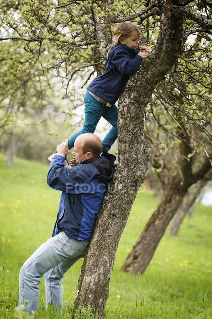 Germany, Baden Wuerttemberg, Father helping daughter to climb tree — Stock Photo