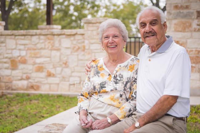 Portrait of senior couple sitting on wall outdoors — Stock Photo