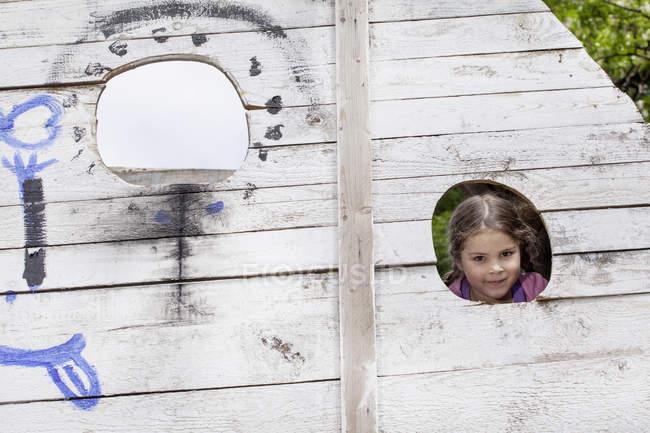 Портрет дівчина, визирав з дірку в дерев'яні стіни майданчик, посміхаючись — стокове фото