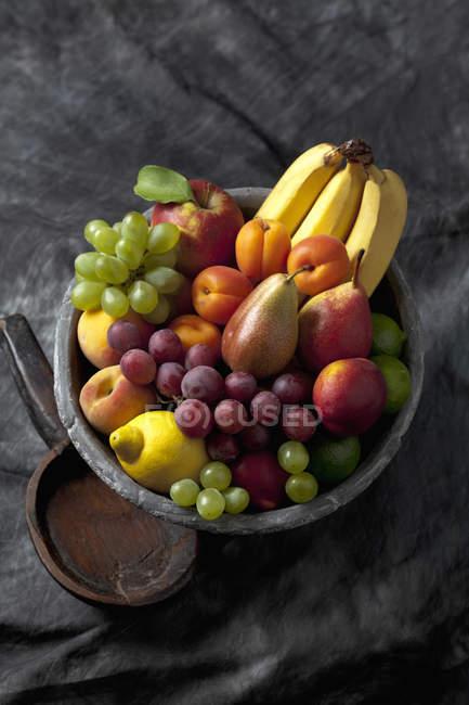 Фруктовая чаша с виноградом, абрикосами, лимоном, бананами, грушами на черной ткани — стоковое фото