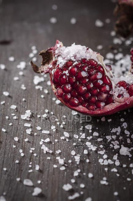 Piece of fresh Pomegranate with coarse sea-salt on dark wood — Stock Photo