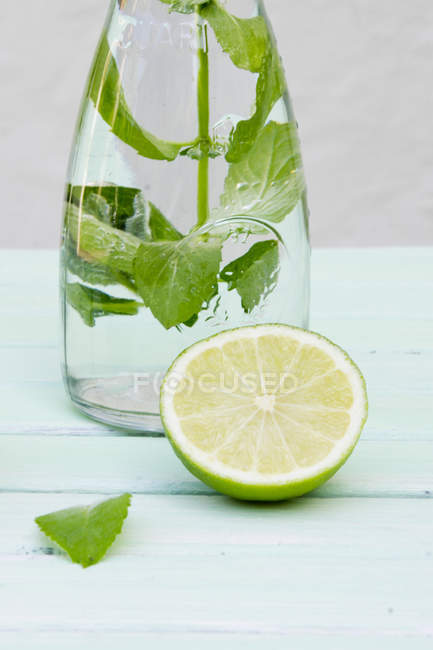 Bottle of lime Lemonade with mint and half of lime on white wood — Stock Photo