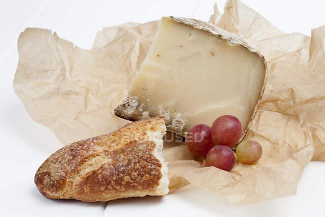 Queso Tomme de Savoie con uvas y baguette en pergamino - foto de stock