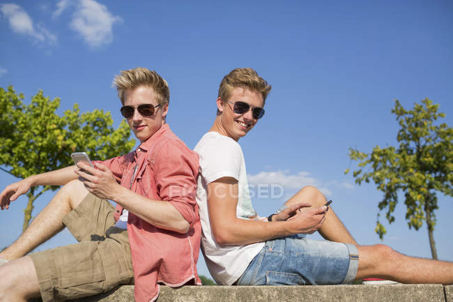 Germany, Two young men sitting on wall using their smart phones — Stock Photo