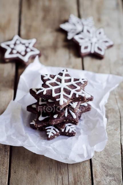 Pila de pan de jengibre en forma de estrella decorado con glaseado de azúcar sobre el papel - foto de stock