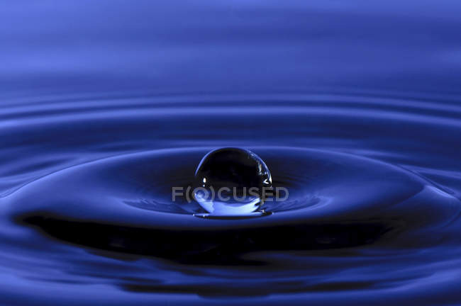 Water drop on blue background — Stock Photo
