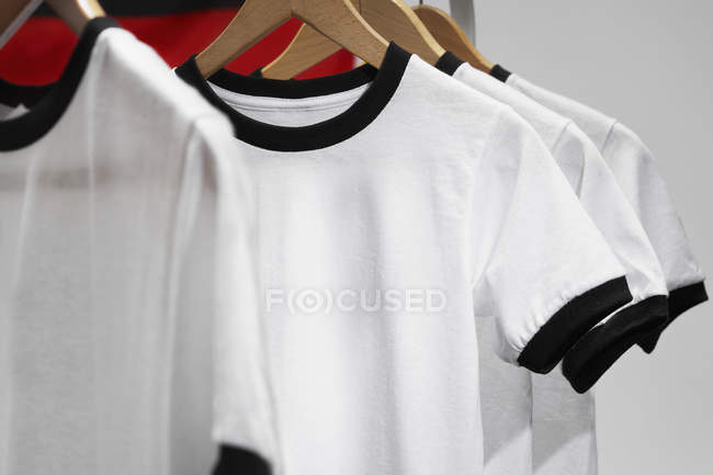 Football shirts on clothes hangers, studio shot — Stock Photo