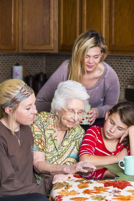 Betagte Frau mit Tablet-Computer inmitten ihrer Familie — Stockfoto