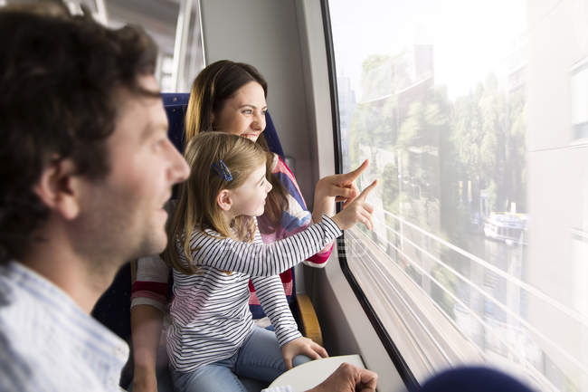 Happy family in a train pointing in window — Stock Photo