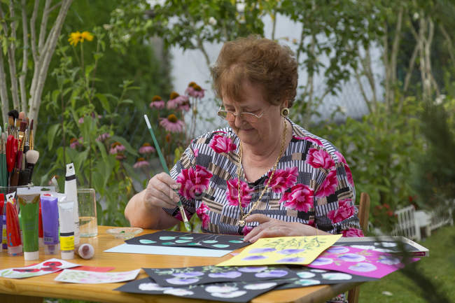 Senior woman painting in garden at daytime — Stock Photo