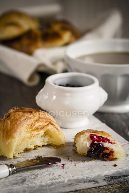 Croissants with milk coffee and jam on wooden board, studio shot — Stock Photo