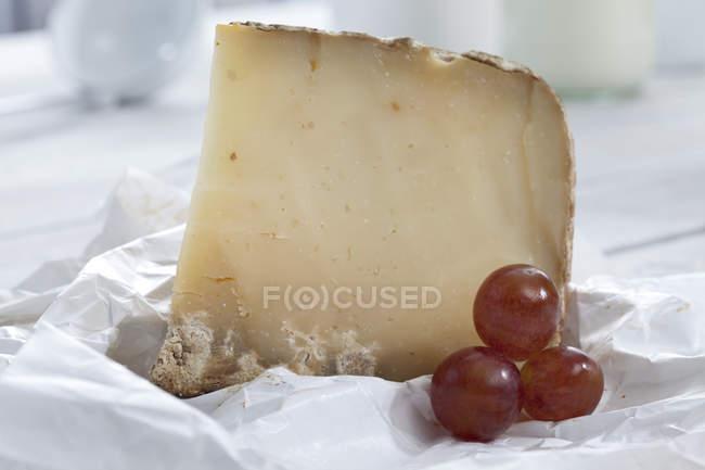 Primer plano del queso de oveja y las uvas en papel - foto de stock
