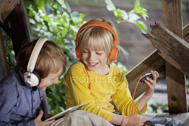 Boys listening music in headphones sitting in wooden tree house at playground — Stock Photo