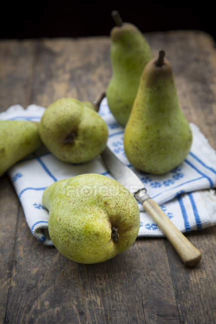 Fresh ripe pears with cloth and knife on dark wood — Stock Photo
