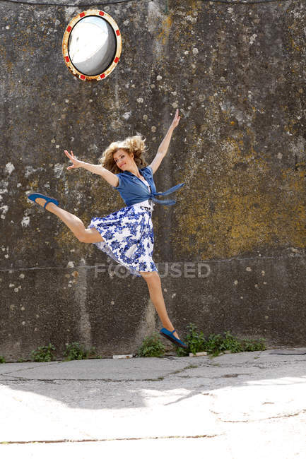 Young woman dancing and jumping in the air — Stock Photo