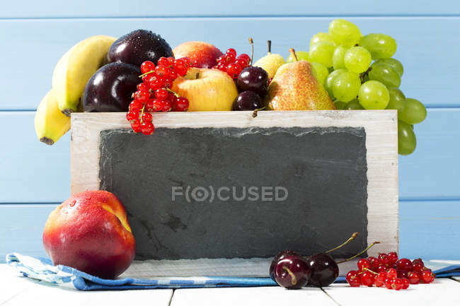 Wooden box with variety of fresh fruits on table — Stock Photo