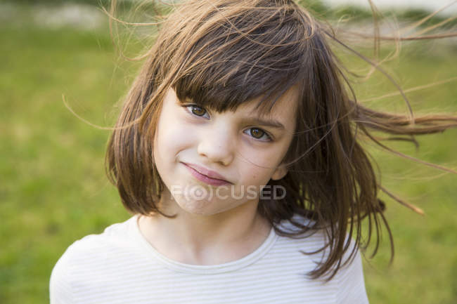 Smiling girl looking at camera in garden — Stock Photo