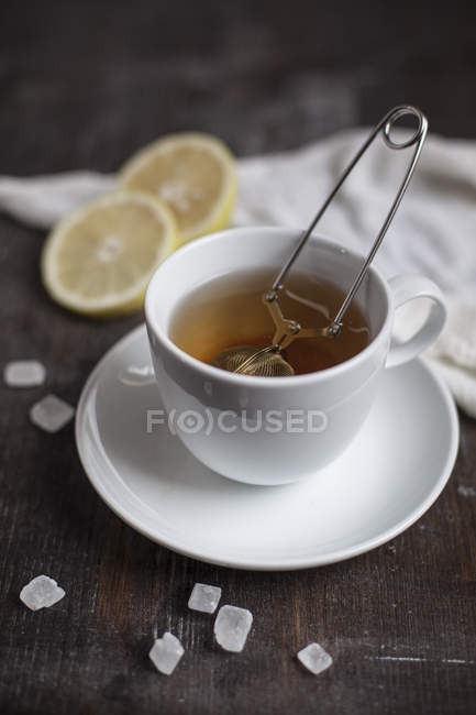 Preparation for tea with tea strainer in cup, slices of lemon, rock sugar on wooden table, studio — Stock Photo