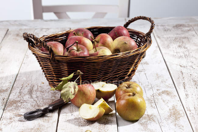 Organic apples with basket and knife on white wooden table — Stock Photo