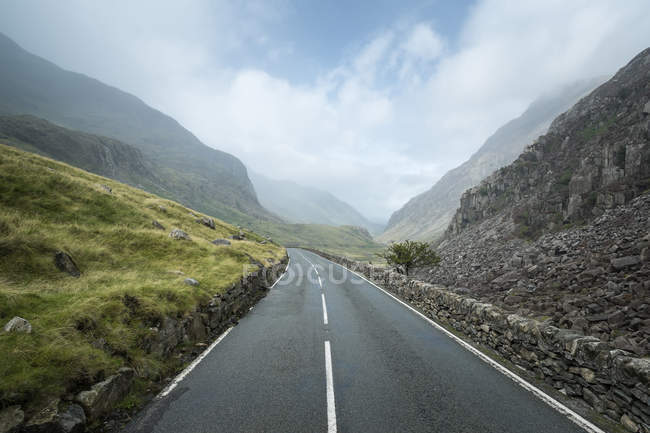 Великобритания, Уэльс, Road Pass at Snowdonia National Park, among mountains and cloudy sky on background — стоковое фото