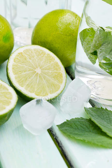 Пляшка вапна лимонад з м'яти і роздвоєна і в цілому Лайми на білого деревини — стокове фото