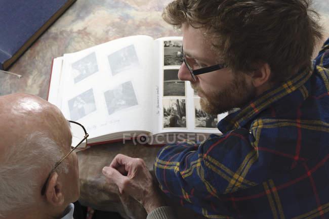 Grandfather and grandson looking photo album, closeup — Stock Photo