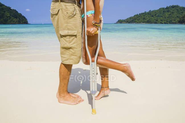 Thailand, Koh Surin island, woman with crutches kissing man at the white sandy beach — Stock Photo
