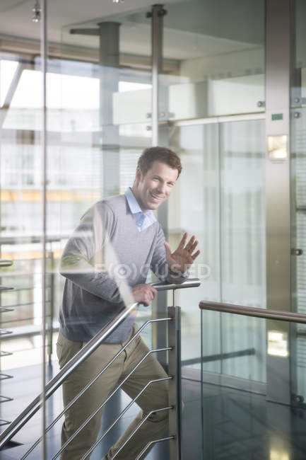 Mid adult man standing on staircase, smiling — Stock Photo