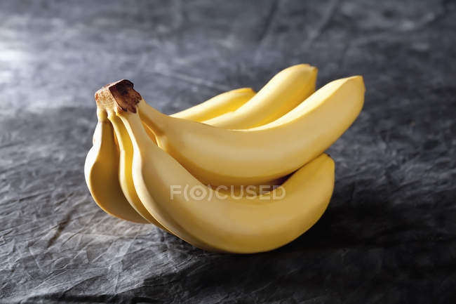 Bunch of fresh bananas on black fabric — Stock Photo