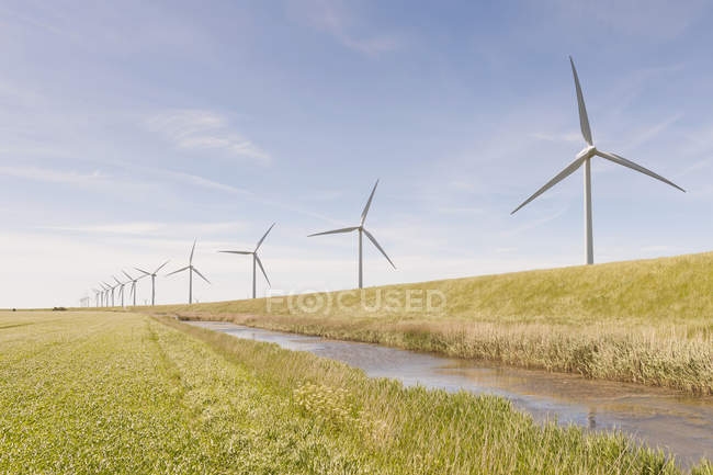 Germany, Schleswig-Holstein, View of wind turbines in green field — Stock Photo