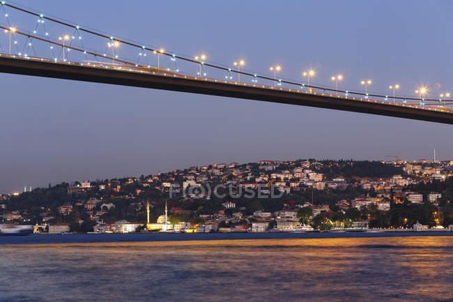 Turkey, Istanbul, View of Bosphorus Bridge and Beylerbeyi Mosque in background illuminated at twilight — Stock Photo