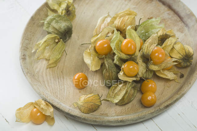 Physalis fruits with dried flowers on wooden plate — Stock Photo