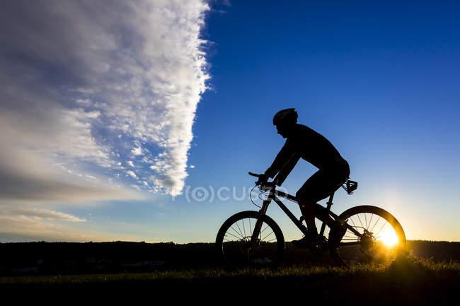 Чоловічий велосипедист на гірському велосипеді на заході сонця — стокове фото