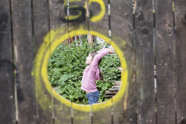 Дівчинка грає в майданчик, вид через отвір в дерев'яні стіни — стокове фото