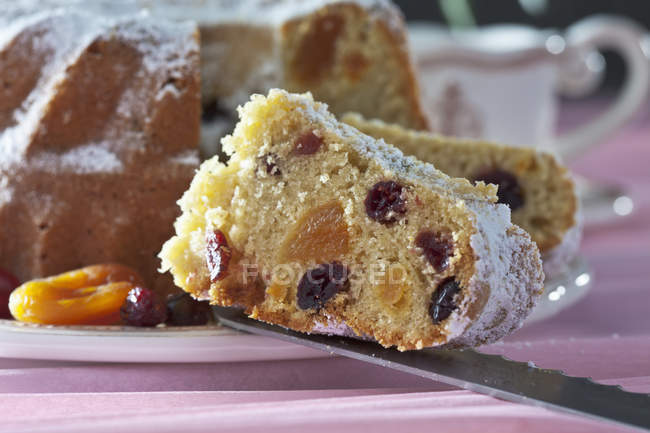 Slice of homemade ring cake with cranberries and apricots with powdered sugar on knife — Stock Photo