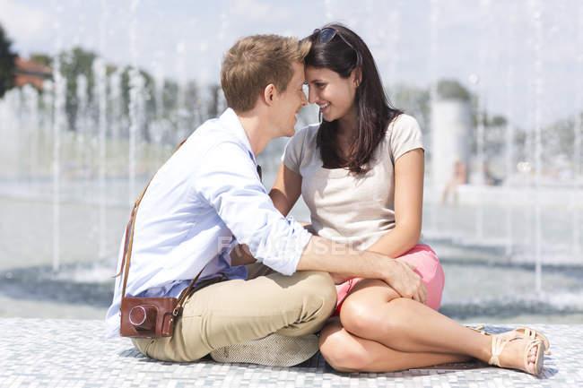 Польша, Варшава, Молодая пара, обнимающаяся у фонтана — стоковое фото