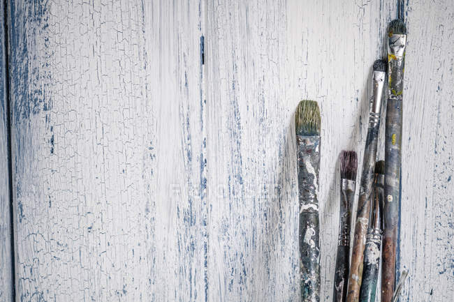 Old brushes leaning on wooden boards — Stock Photo