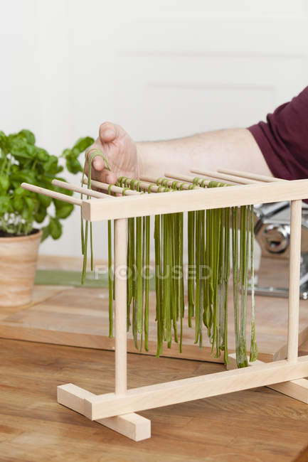 Man preparing green tagliatelle, basil in pot on background — Stock Photo