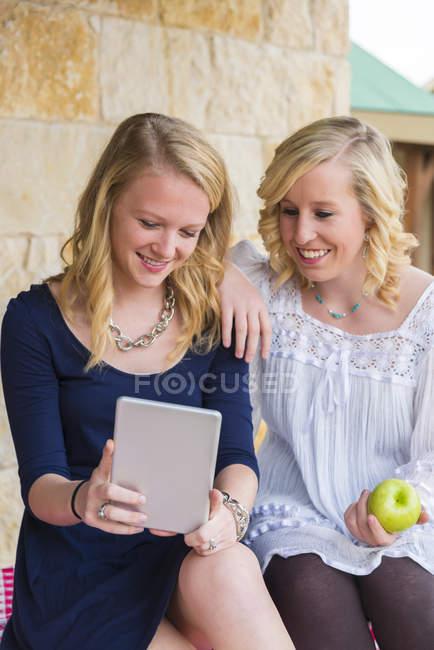 Teenage girls using mini digital tablet — Stock Photo