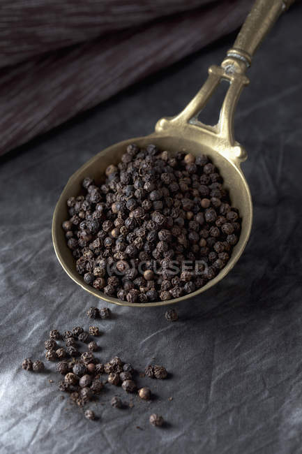 Brass spoon with black peppercorns on textile, close up — Stock Photo