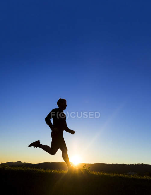 Silueta de hombre jogger al atardecer - foto de stock