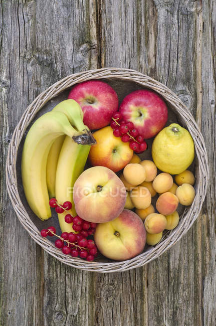 Корзина фруктов яблоки, бананы, персики, красной смородины и лимон на потертом древесины — стоковое фото