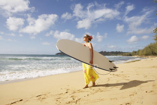 USA, Hawaii, Woman standing with surfboard on beach — Stock Photo