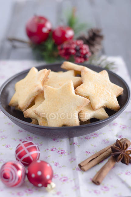 Star-like christmas cookies in bowl and decorations on table — Stock Photo