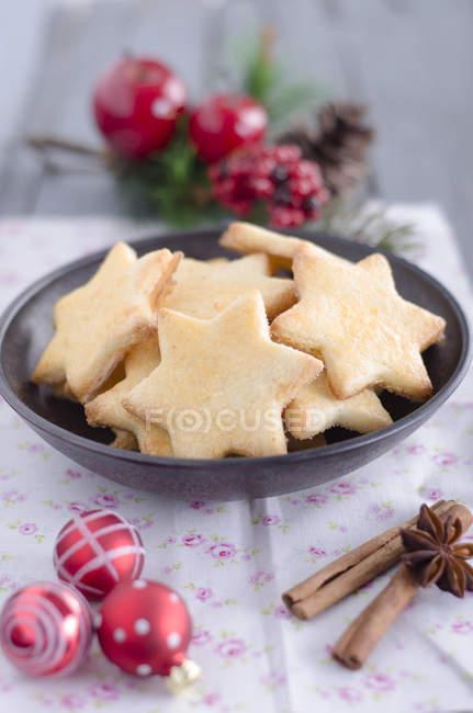 Sternförmige Weihnachtsplätzchen in Schüssel und Dekorationen auf Tisch — Stockfoto