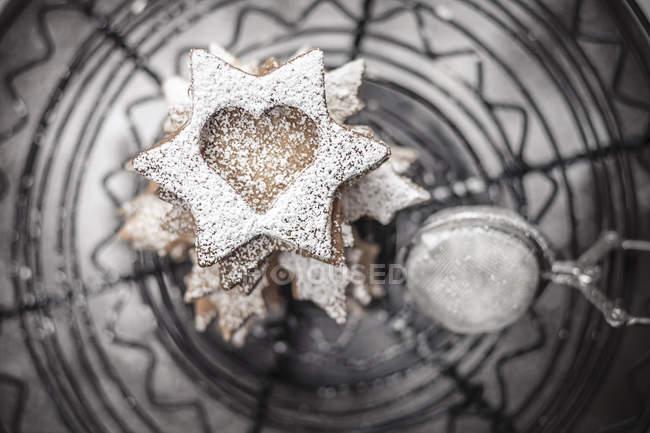 Com açúcar em pó polvilhado biscoitos de Natal e coador deitado no carrinho de bolo, close-up — Fotografia de Stock