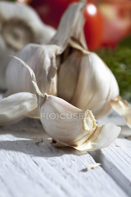 Primer plano de dientes de ajo frescos en la superficie de madera blanca - foto de stock