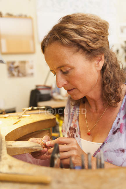 Mature woman working on ring in her workroom at home — Stock Photo
