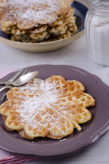 Макро-в форме сердца вафли с пудрой сахара на плите с столовые приборы — стоковое фото