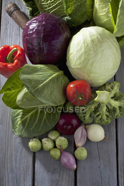 Cabbage varieties and vegetables on grey wooden table — Stock Photo